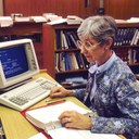 An photograph from the Cancer Visuals Online project of a librarian at the National Library of Medicine using a computer to access the Physicians Data Query (PDQ), used as an emblematic image for EDRN's common data elements (CDEs).